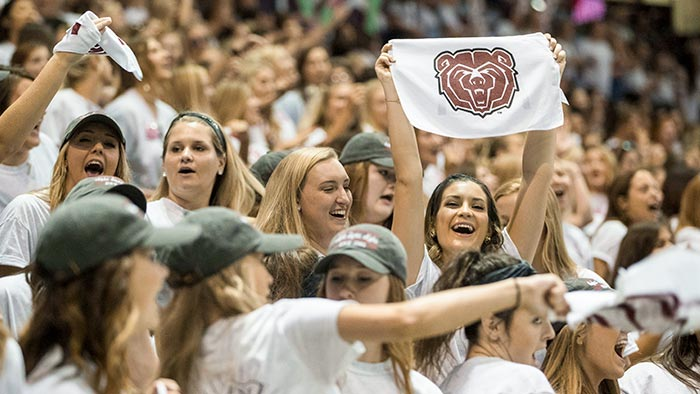 Student holding a Bear head flag among a large group of students.