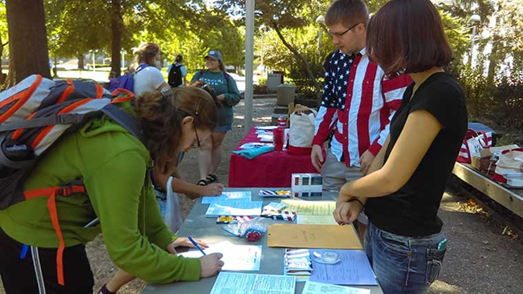 Students supervising a voter registration table.