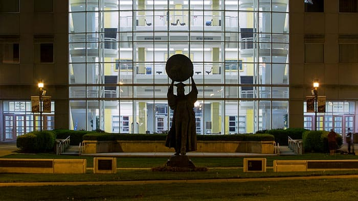 Evening view of Citizen Scholar statue backlit by Strong Hall
